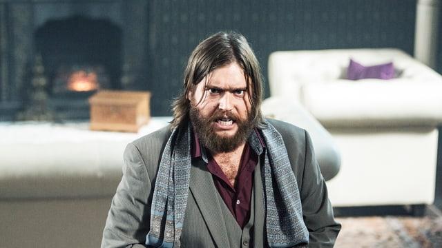 Mann mit Vollbart und langen Haaren blickt wütend in die Kamera.