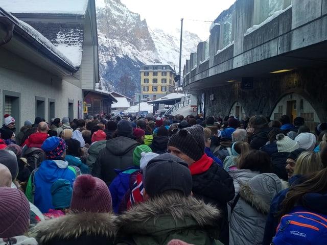 Viele Menschen in einer Strasse, im Hintergrund Blick auf Berge