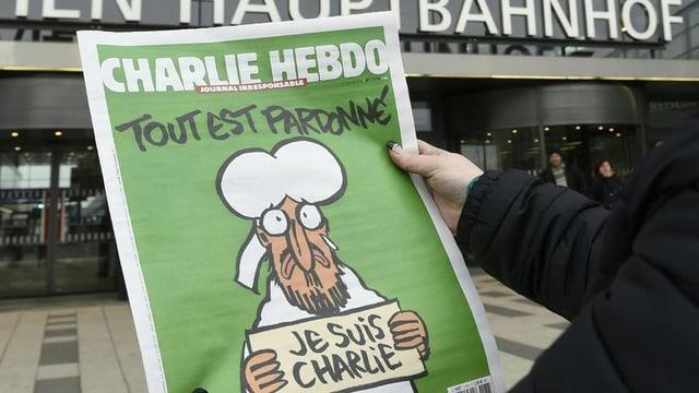 """Il frontispizi da l'ultima ediziun da """"Charlie Hebdo"""": """"Tut è perdunà"""" – er Mohammed bragia per las victimas da l'attentat."""