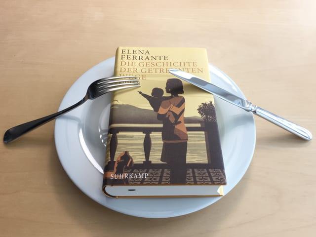 Der Roman «Die Geschichte der getrennten Wege» von Elena Ferrante liegt auf einem Teller