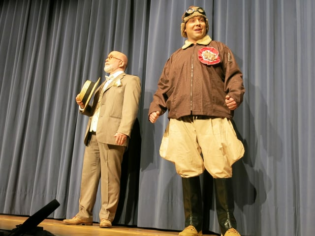 Älterer Herr mit Bart und Anzug sowie jüngerer Mann mit Fluglederjacke und Lederhelm.