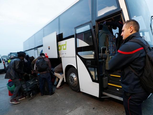 Flüchtlinge packen ihre Koffer in einen Reisecar.