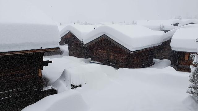 Eine Gruppe von Holzhäusern mit riesigen Schneemengen auf den Dächern.