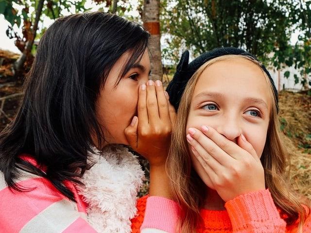 Zwei Mädchen flüstern.