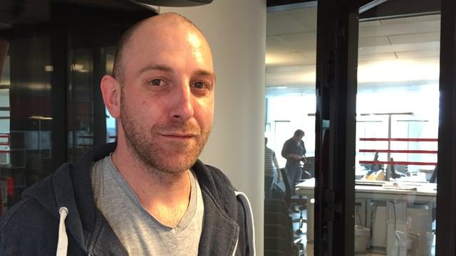 Junger Mann mit Glatze und Dreitagesbart im Radiostudie