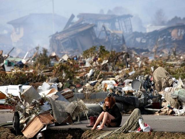 Frau umgeben von Trümmern