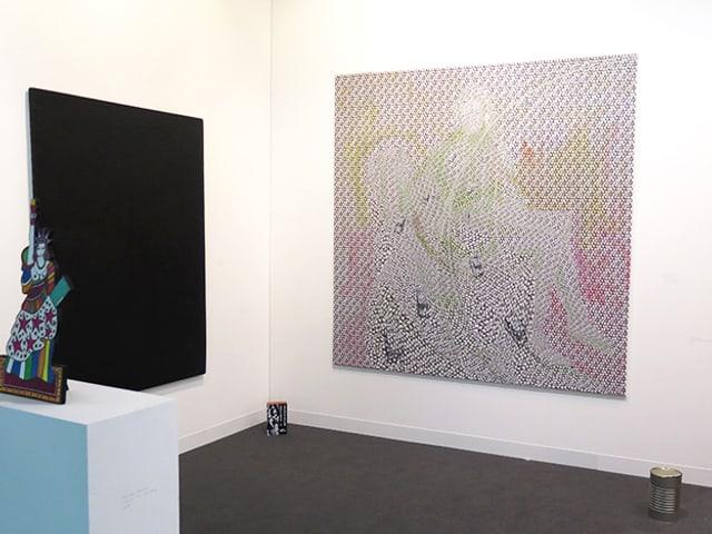 Ein Galeriestand mit einer Skulptur und zwei Bildern.