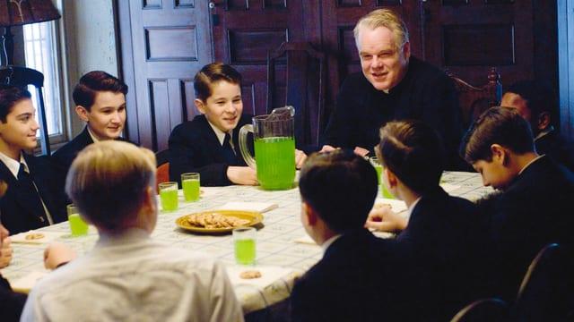 Ein Pastor sitzt mit einer Gruppe Jungen am Esstisch.