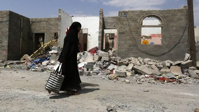 Frau geht durch Ruinen in Jemens Hauptstadt Sanaa.