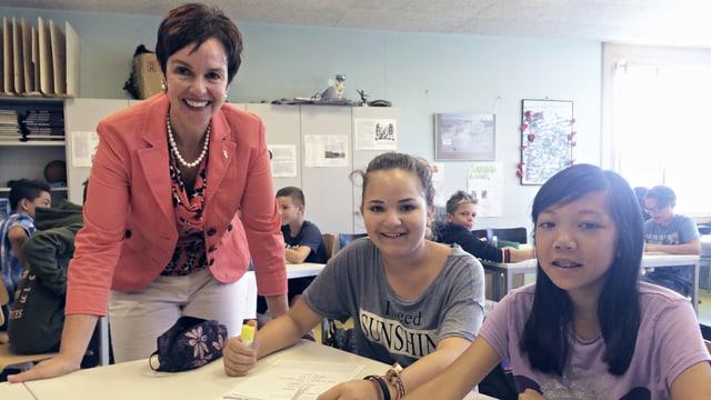 lachende Frau mit rotem Jacket und zwei Schülerinnen