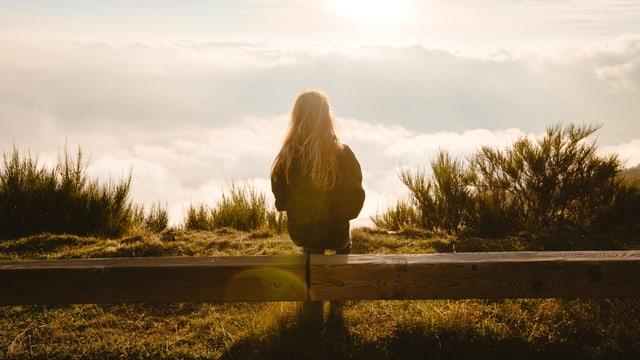 Eine junge Frau sitzt auf einer Bank. Vor ihr ist ein Wolkenmeer zu sehen.