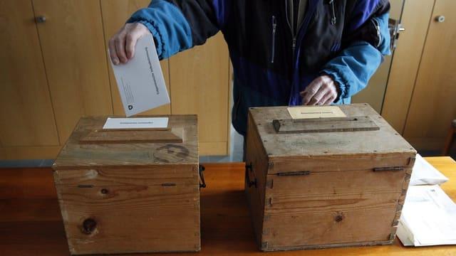 duas urnas per votar, ina persuna metta ses cedel en l'urna
