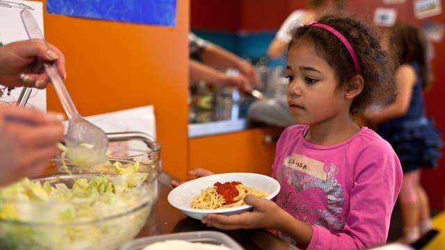 Mädchen bekommt Essen auf Teller