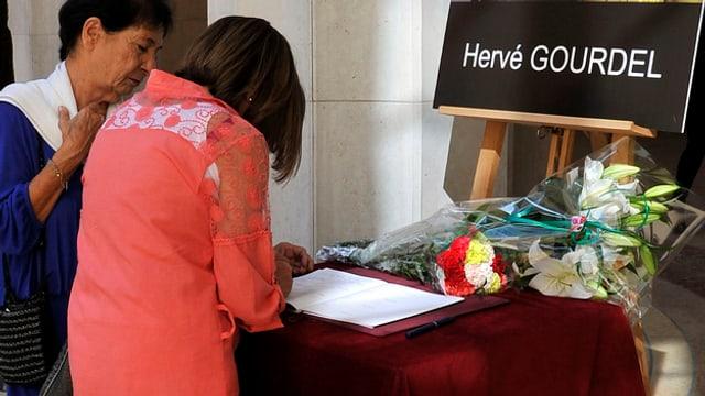 Zwei Frauen tragen sich in ein Kondolenzbuch für den ermordeten Bergführer ein.
