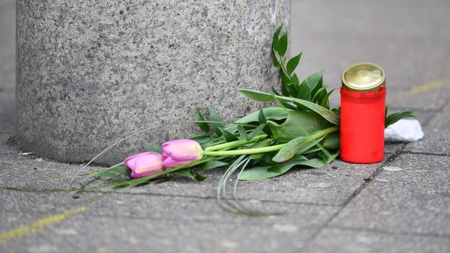 Blumen und Kerze auf einem Trottoir in Heidelberg.
