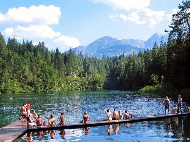 Am Crestasee in Graubünden sitzen Leute auf dem Steg.