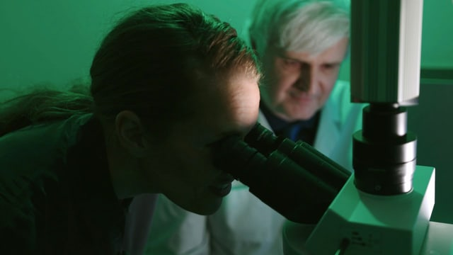 Frau schaut durchs Mikroskop.