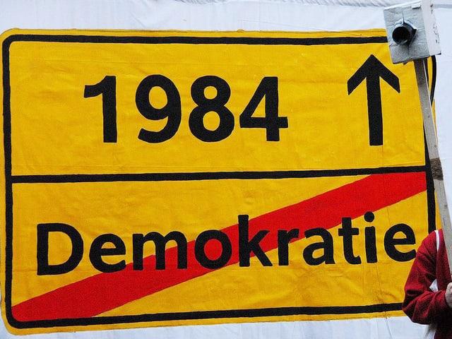 Verkehrsschild mit «1984» und dem Wort Demokratie durchgestrichen als Ortsausfahrt.
