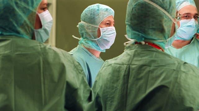 Vier Ärzte in OP-Kittel und Mundschutz in einem Schweizer Spital (Archivbild).
