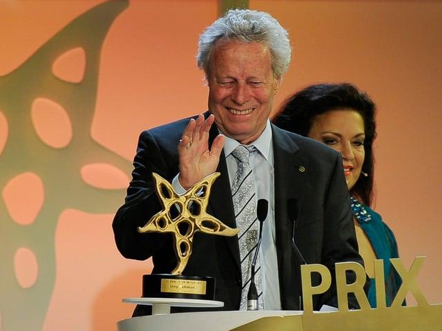 Beny Rehmann mit erhobener Hand vor dem Mikrofon und der Sternenskulptur.