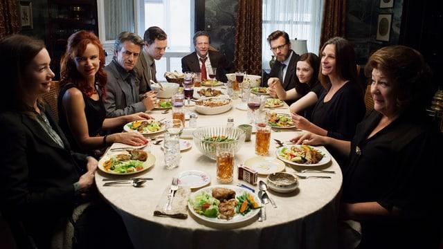 Eine Familie ist um einen reichlich gedeckten Esstisch versammelt.