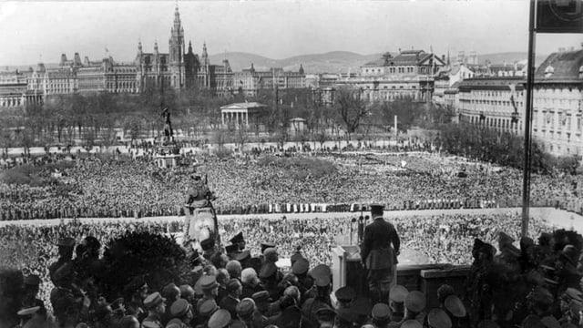 Schwarz-weiss Aufnahme mit Hitler von hinten im Vordergrund und einer Menschenmasse im Hintergrund.