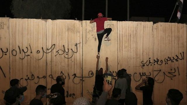 Jemand klettert auf die Mauer um das iranische Konsulat in Kerbela.
