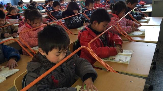 Eine chinesche Schulklasse beim Schreiben mit Metallbügeln als Distanzhalter.