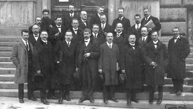 Männer stehen zusammen für ein Gruppenfoto. Alle in schwarzen oder grauen Anzügen.