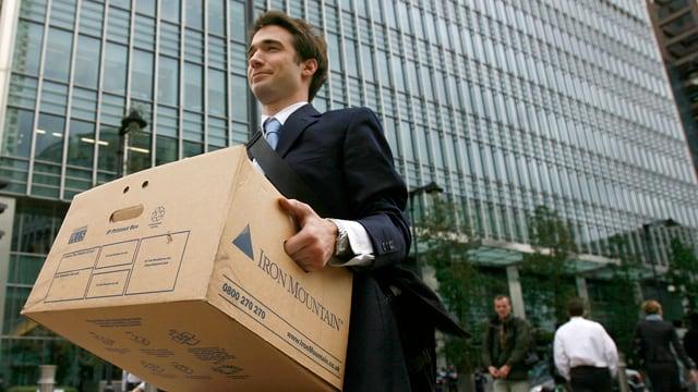 Banker, der eine Kartonschachtel trägt