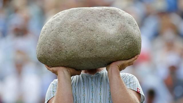 Ein Sportler stemmt einen sehr grossen Stein auf seinen Händen.