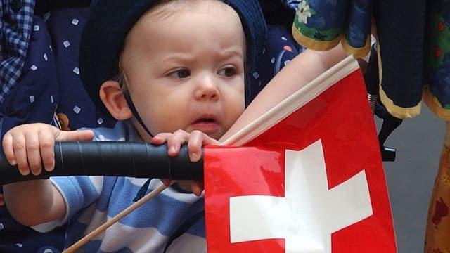Kritisch drinblickendes Kleinkind mit Schweizer Fahne im Kinderwagen
