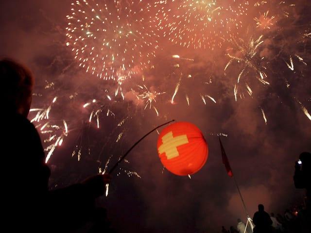 Links der Schatten eines Jungen mit Lampion in der Hand in rot mit Schweizerkreuz. Der Himmel ist voller heller Funken von Feuerwerk. Sonst ist das Foto dunkel.
