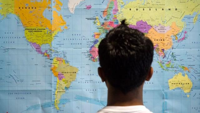 Ein Mann betrachtet eine Weltkarte.