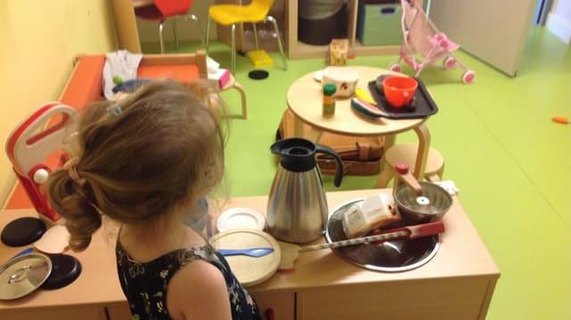 Mädchen in der MINT-Kita steht in Spielküche
