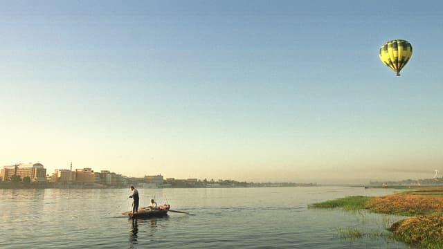 Ein Fischerboot treibt auf dem Nil, darüber ein Heissluftballon.