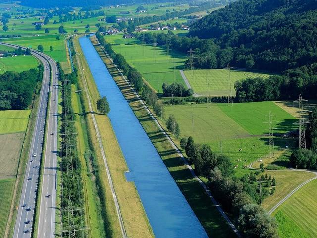 Fluss von oben, daneben grüne Wiesen und Autobahn.