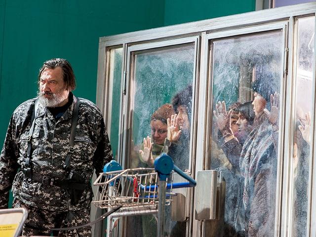 Ein bärtiger Mann im Tarnanzug, zu seiner Linken drücken Menschen ihre Hände an verschlossene Glastüren.