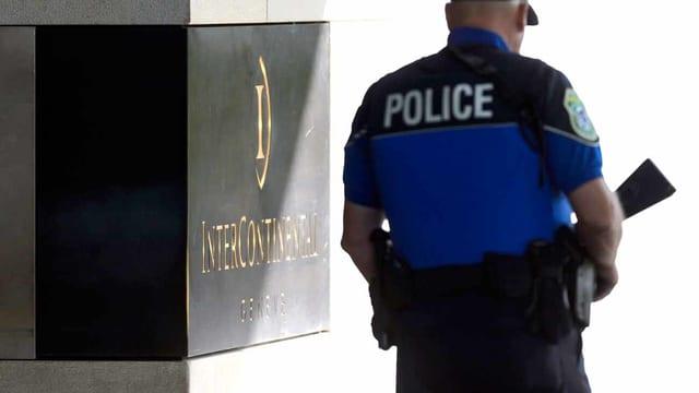 Ein Polizist steht vor einem Genfer Hotel, in dem die Gespräche stattgefunden haben.