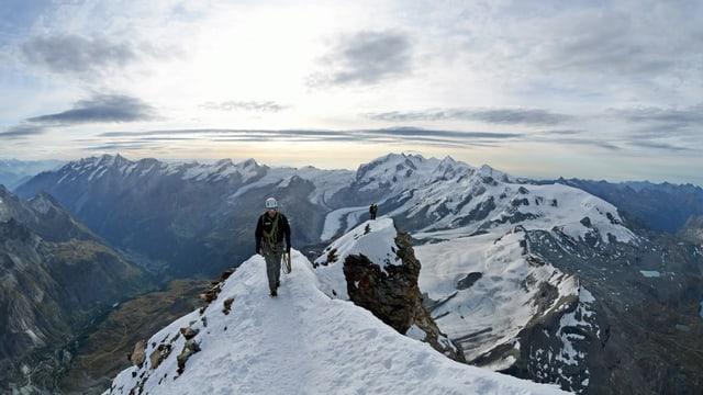 Ein Bergsteiger auf einem verschneiten Grat.
