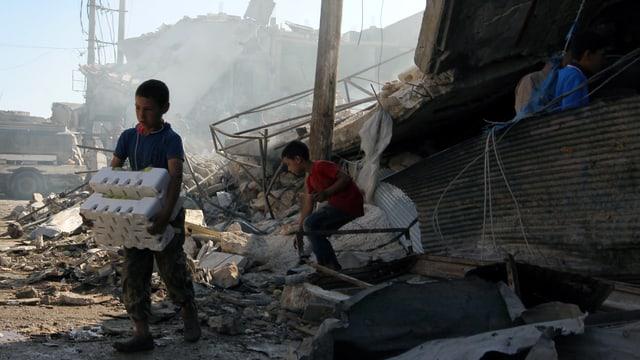 Zwei Kinder sichern Ware nach einem Luftangriff in Atareb in der Provin Aleppo.