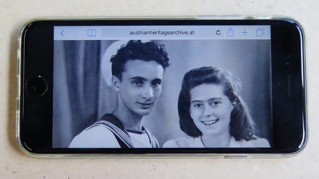 Auf einem Smartphone ist ein schwarz-weiss-Foto mit einem Paar zu sehen.