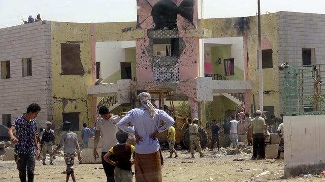 Menschen stehen vor einem beschädigten Gebäude.