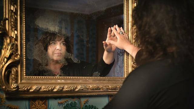 Eine Frau guckt in einen alten Spiegel.