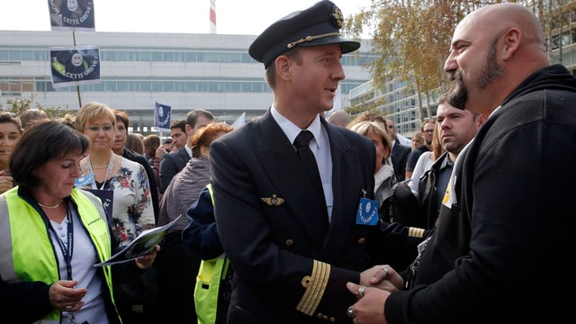 Streikender Air-France-Pilot spricht an einer Kundgebung mit einem Passanten