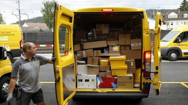 In auto da La Posta cun en pachets ed in um che serra la porta davostiers.