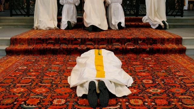 Bischof Huonder liegt auf dem Bauch während der Weihe.