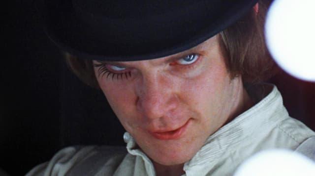 Alex mit weissem Hemd und schwarzem Hut, die rechte Wimper stark geschmickt, blickt bedrohlich in die Kamera.