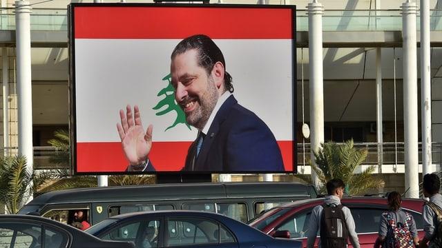 Hariri lächelt und winkt von einem Plakat in einer Strasse in Beirut.