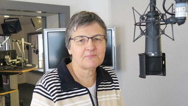Eine Frau steht im Radiostudio vor einem Mikrophon.